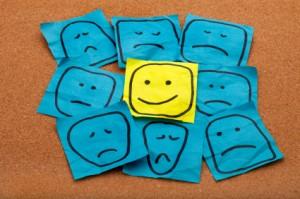 Нарисувани тъжни лица с едно усмихнато лице в средата
